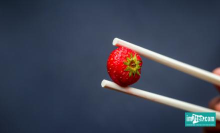 Eine Erdbeere wird nur mit Asiastäbchen angefasst - denn die Erdbeerwoche steht als Synonym für die Menstruation.