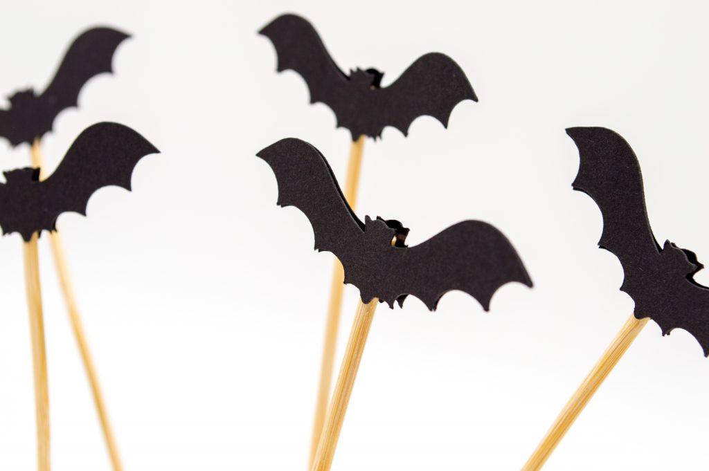 selbst gebastelte Fledermäuse aus schwarzem Fotokarton auf Schaschlikspießchen als Halloween-Deko